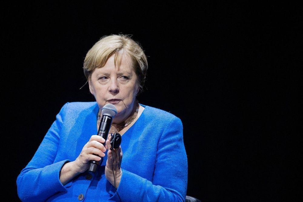 Angela Merkel med en skrigende blå jakke og et alvorligt blik