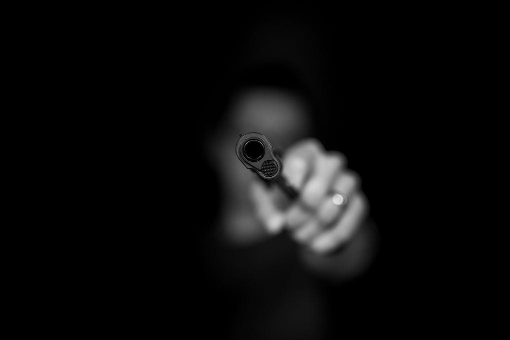 En hånd med en pistol der peges direkte mod kameraet.