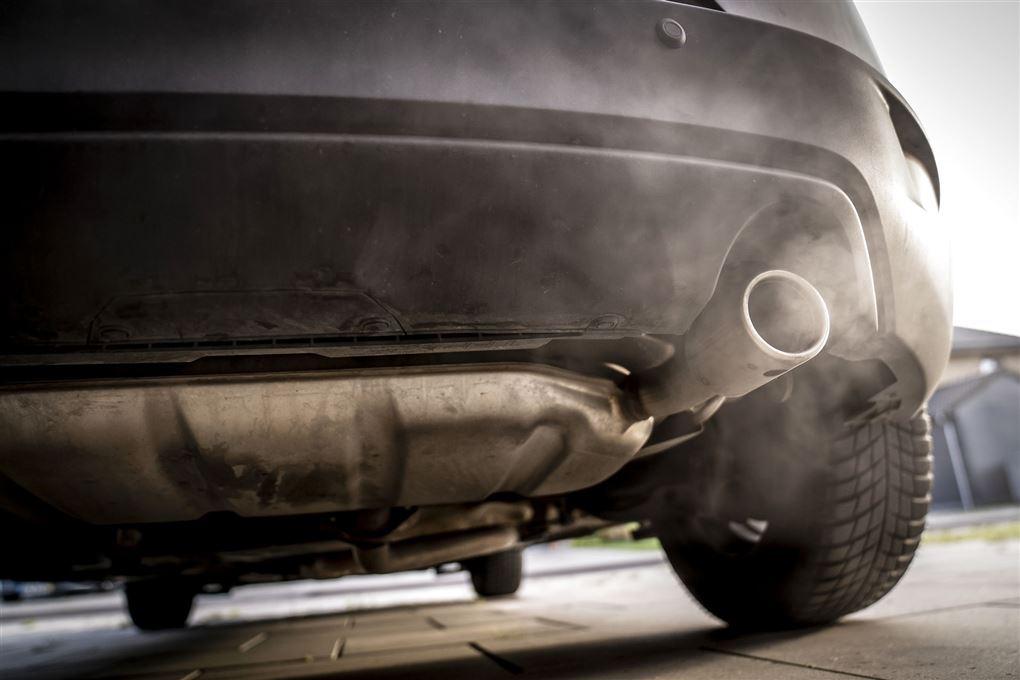 En osende udstødning på en sort bil fotograferet nedefra.
