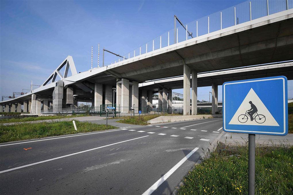 En flersporet stor vej med en cykelovergang og en vejbro oppe over,