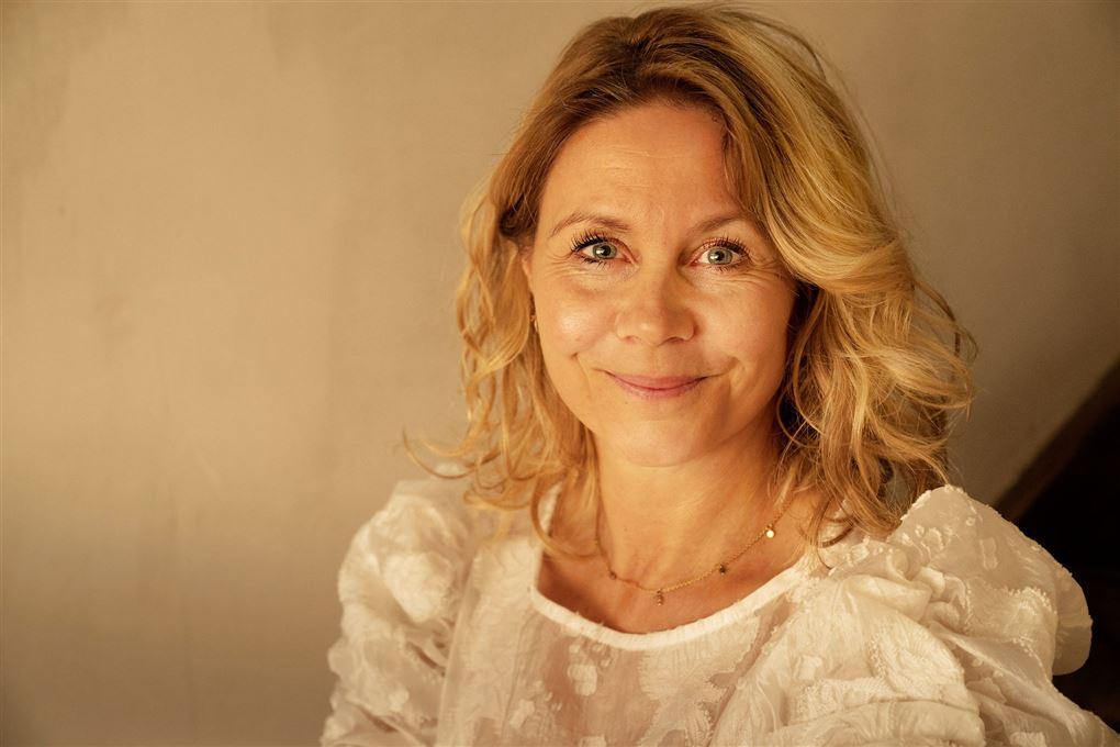 Portræt af Anne Louise Hassing i blødt lys der ligner solopgang og en hvid kjole.