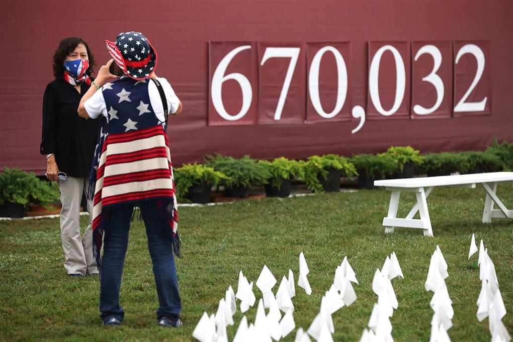 to med maske fotograferer hinaden foran et skilt