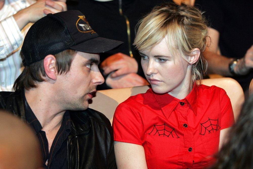 en blond kvinde i rød skjorte og en fyr med sort kasket