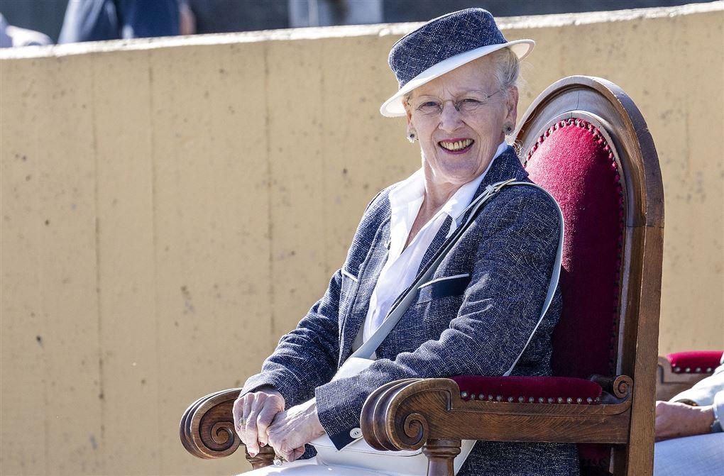 Dronning Margrethe sidder på stol og smiler