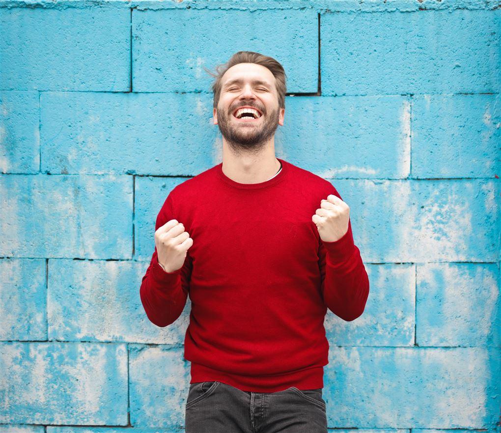 En mand i rød bluse knytter næverne og griner