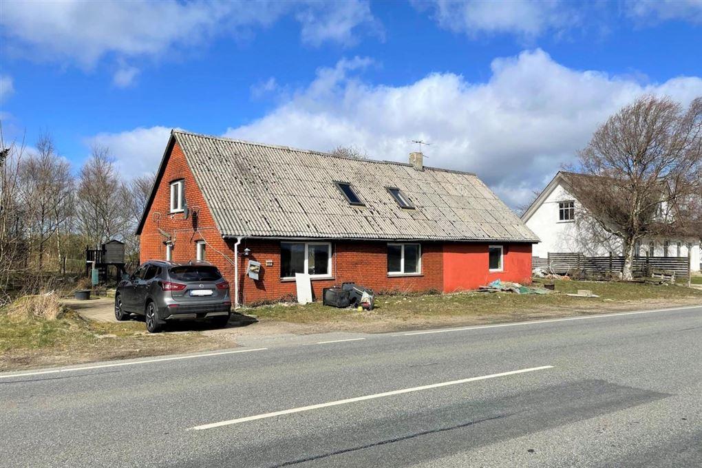 Et faldefærdigt rødstenshus med slidt tag.