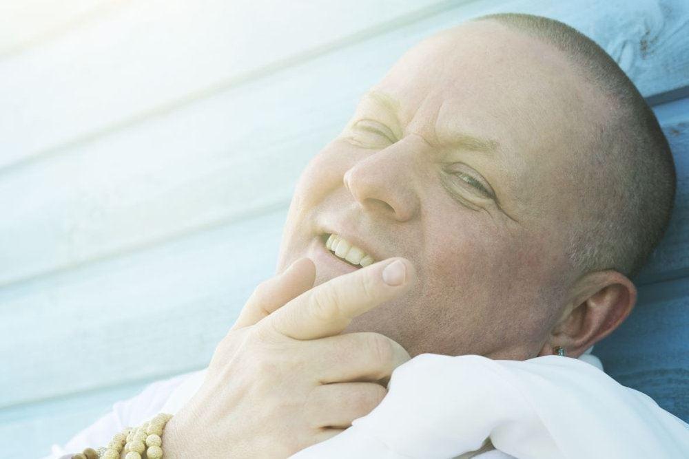 Anders Matthesen med hvidt tøj og et smil der er et guddommeligt lys over ham