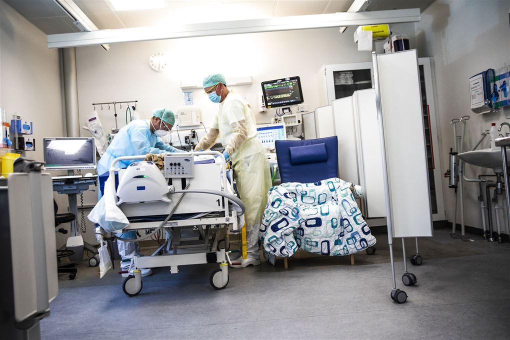 to hospitalsansatte står ved seng med patient
