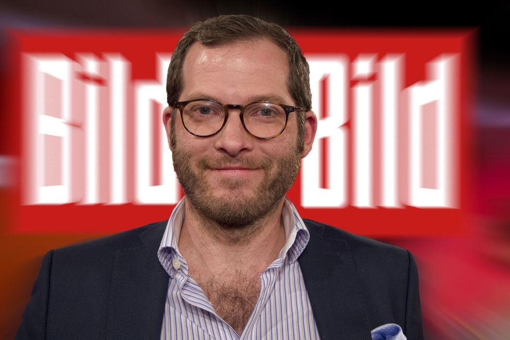 En mand med skæg foran et skilt med Bild