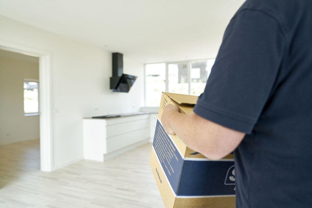 En mand med en flyttekasse i et tomt køkken