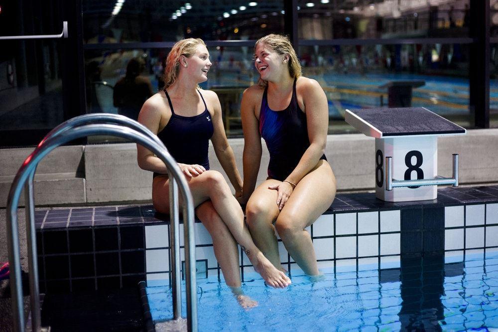 to svømmere sidder på bassinkanten