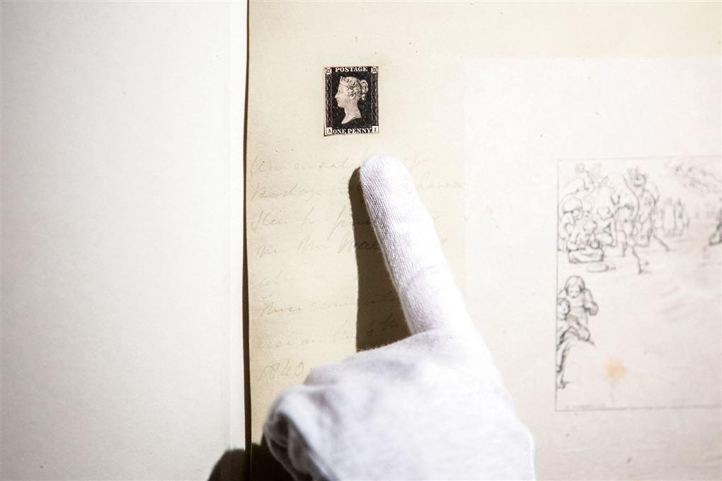 En hånd iført hvid bomuldshandske peger på det lille frimærke.