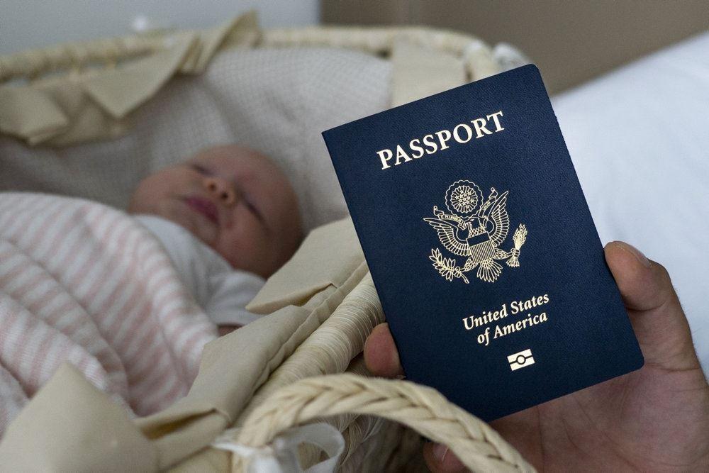 Et mørkeblåt pas foran en lille baby der ligger i en lift